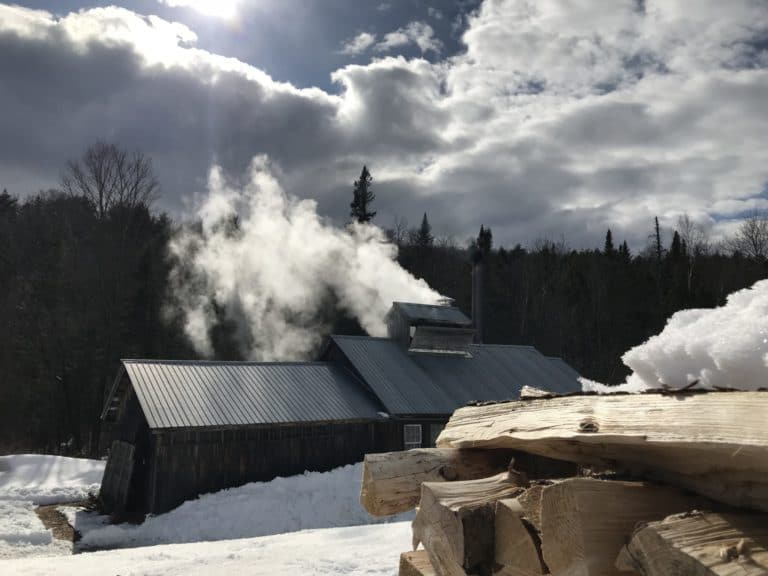 Sinzibukwud Sugarhouse, home of Green Mountain Family Forest. Sugarshack where family makes maple syrup with wood fire. Stack of Firewood in foreground with snow