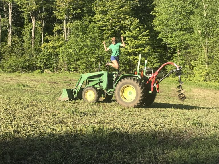 Erin jumping off a tractor