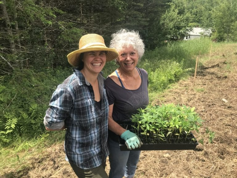 Erin and her grandmother smiling and planting a plug tray full of hemp plants