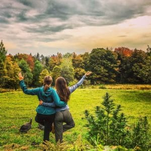 two female yogis practice yoga on a Vermont Autumn hemp farm. A guinea hen looks on while the trees leaves change from green to red and orange